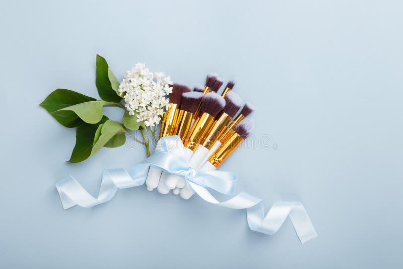 Fije de los cepillos para componen en fondo azul con la floración blanca de la lila imagen de archivo