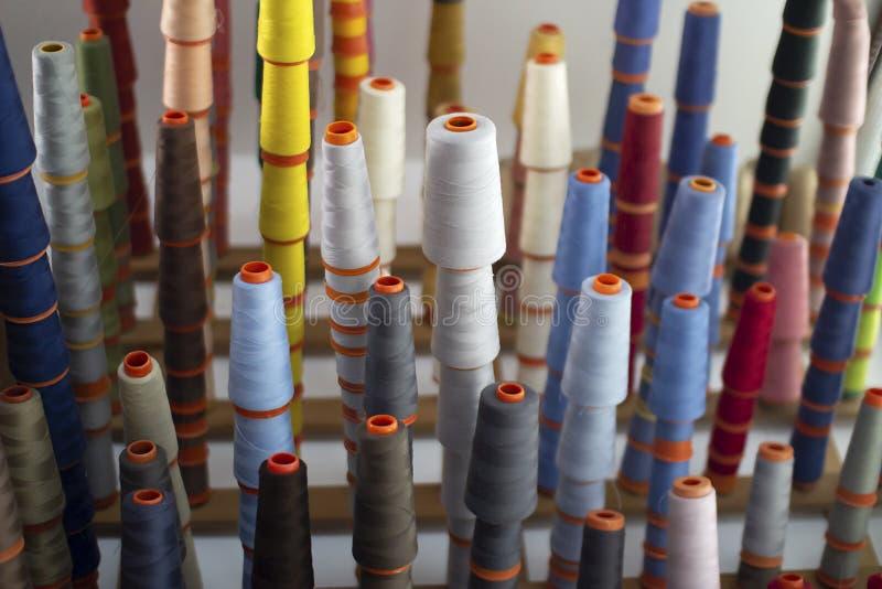 Fije de los hilos coloreados para coser en bobinas fotografía de archivo