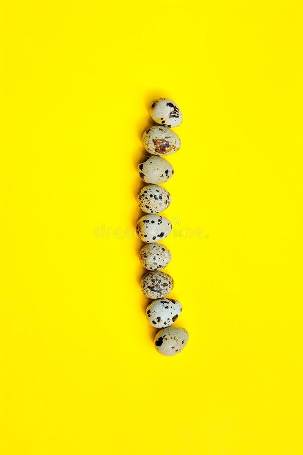Fije de los huevos de codornices del grupo en una línea en un fondo amarillo imágenes de archivo libres de regalías