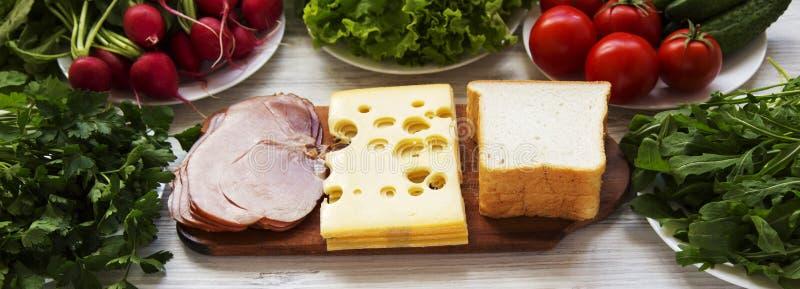 Fije de los ingredientes para hacer el almuerzo escolar: pan, verduras, queso y tocino en la superficie de madera blanca Consumic fotografía de archivo libre de regalías