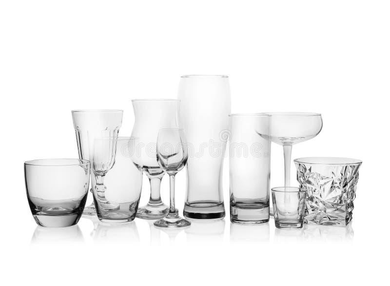 Fije de los vidrios vacíos para diversas bebidas en blanco imagen de archivo