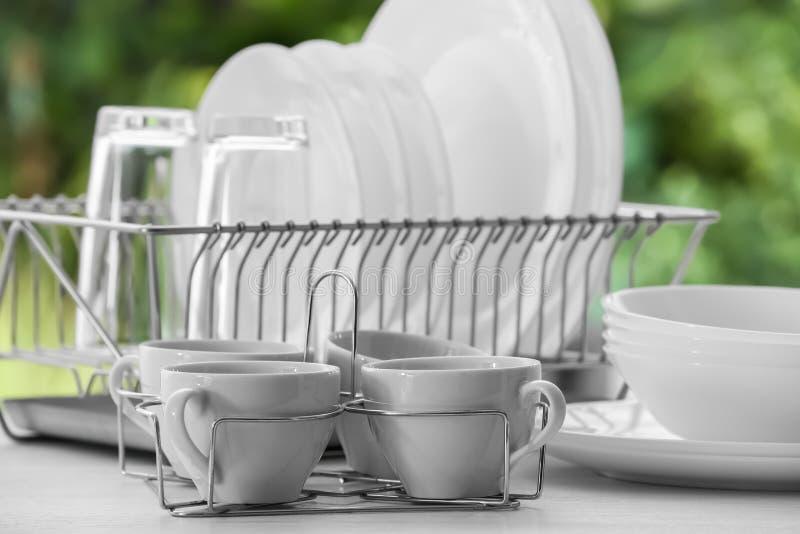 Fije de platos, de vidrios y de tazas limpios en la tabla foto de archivo libre de regalías