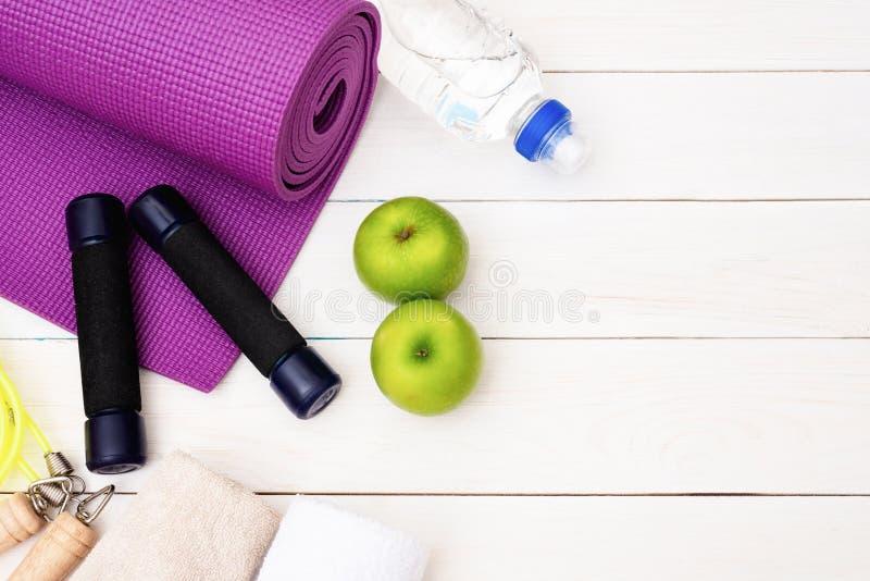 Fije de práctica de la yoga con la estera púrpura, la pesa de gimnasia, la toalla, la botella de agua y la manzana verde, comba E fotos de archivo libres de regalías