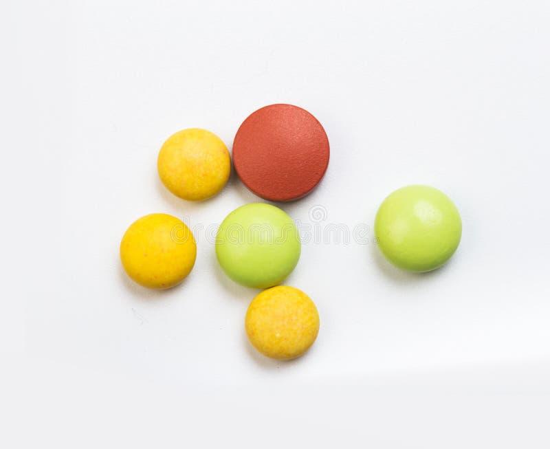 Fije de tabletas multicoloras en un fondo blanco imagen de archivo