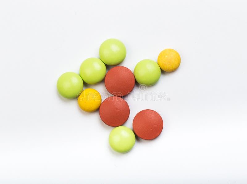 Fije de tabletas multicoloras en un fondo blanco foto de archivo