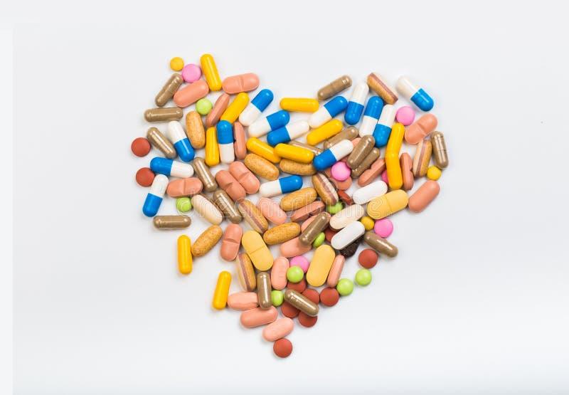 Fije de tabletas y de cápsulas multicoloras en una forma blanca de la forma del corazón del fondo - imagen imagen de archivo libre de regalías