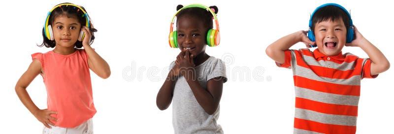 Fije de tres niños multirraciales con los auriculares aislado fotos de archivo