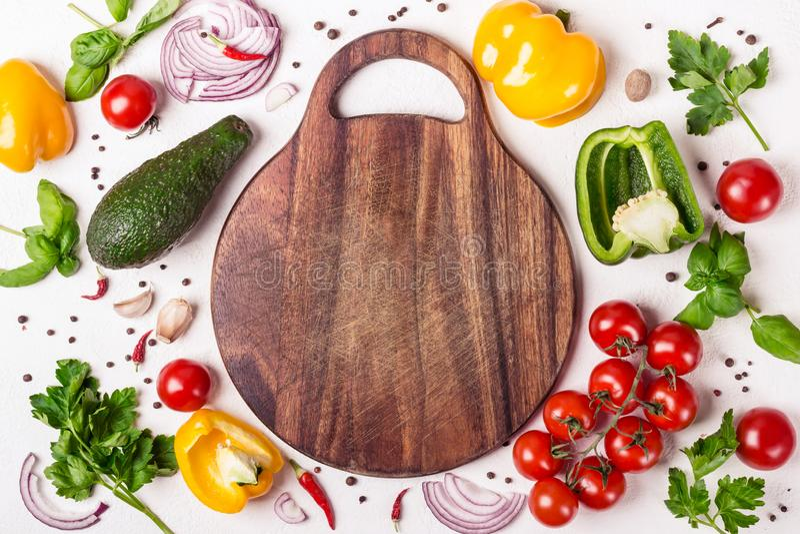 Fije de verduras y de hierbas alrededor de una tabla de cortar de madera Concepto europeo de la cocina y el cocinar fotografía de archivo libre de regalías