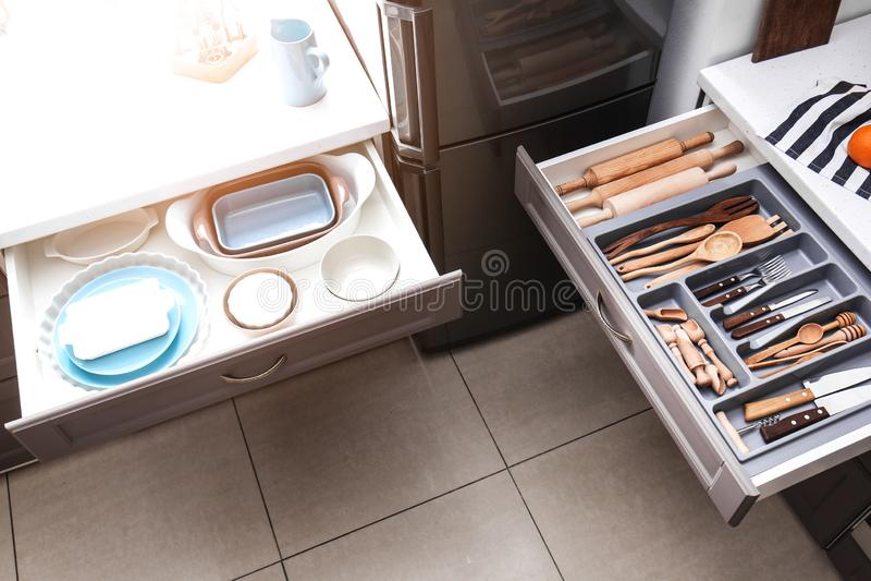 Fije del artículos de cocina y de los utensilios limpios en cajones imagen de archivo