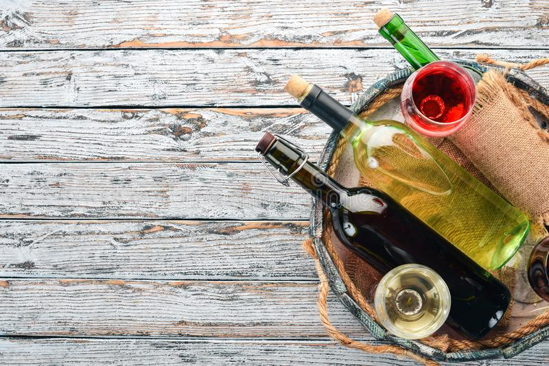 Fije del vino blanco rojo y en botellas y vidrios uva En un fondo de madera blanco Espacio libre para el texto imagen de archivo