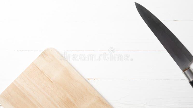 Fije el cuchillo en la tarjeta de corte imagen de archivo