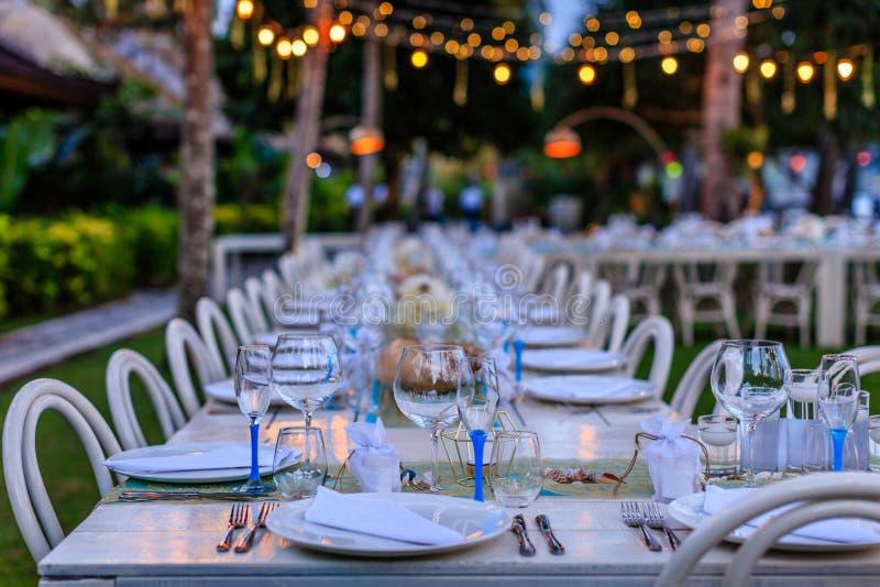 Fije la tabla para una cena de boda blanca y azul de playa adornada con las cáscaras, luces de la tarde imagenes de archivo