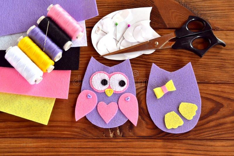 Fije para coser un búho del fieltro, plantillas de papel, hojas del fieltro, tijeras, hilo, aguja, pernos en un fondo de madera m imagenes de archivo