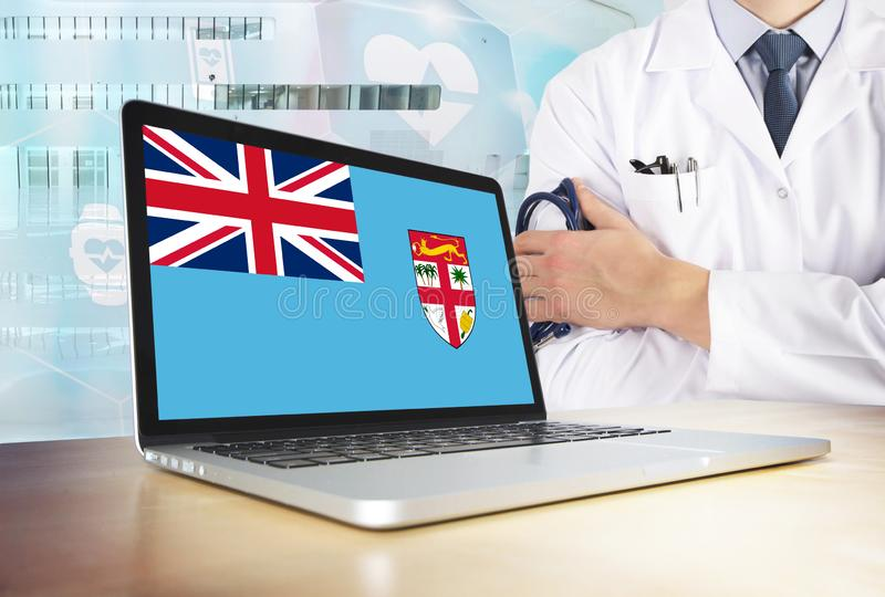 Fiji healthcare system in tech theme. Fijian flag on computer screen. Doctor standing with stethoscope in hospital. Cryptocurrency. And Blockchain concept stock images