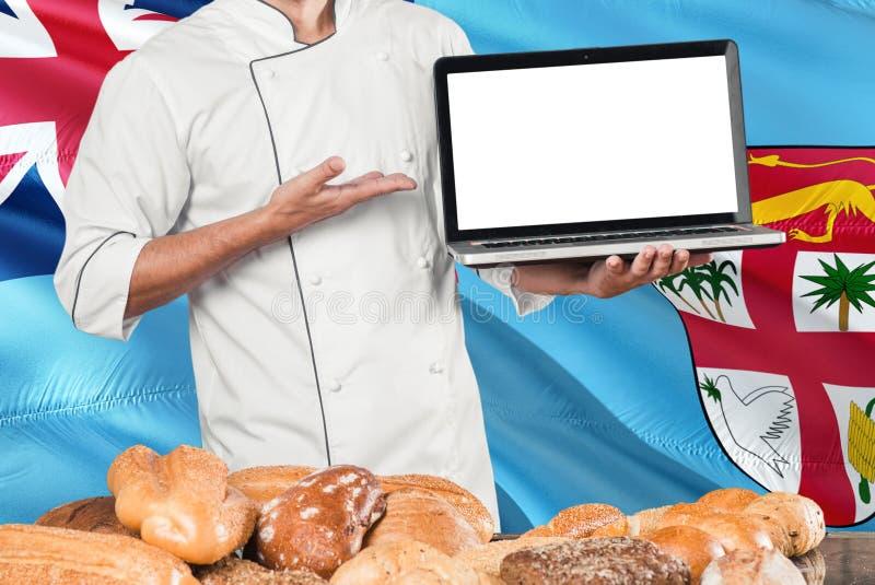Fijian bagareinnehavbärbar dator på fijiansk flagga- och brödbakgrund Bärande likformig för kock som pekar den tomma skärmen för  royaltyfria foton