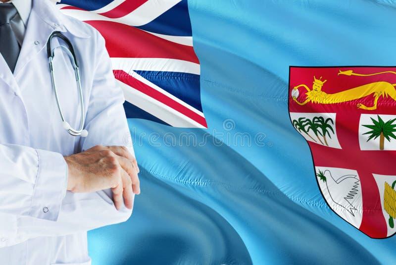 Fijian doktorsanseende med stetoskopet på fijiansk flaggabakgrund Nationellt v?rdsystembegrepp, medicinskt tema arkivbilder