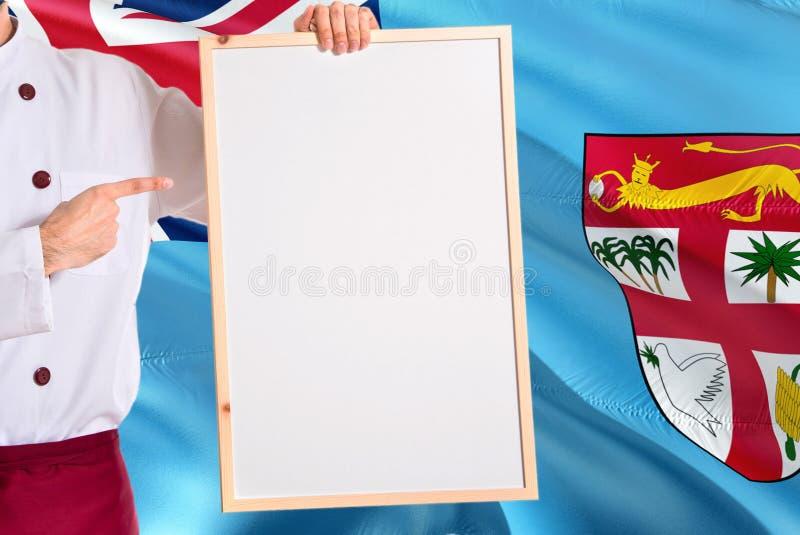 Fijian kock som rymmer den tomma whiteboardmenyn på fijiansk flaggabakgrund Laga mat den bärande likformign som pekar utrymme för royaltyfri bild