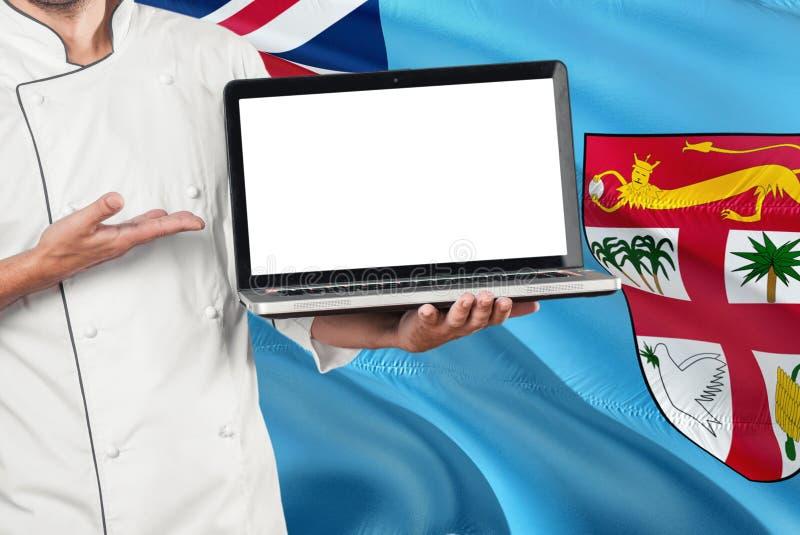 Fijian kockinnehavbärbar dator med den tomma skärmen på fijiansk flaggabakgrund Laga mat den bärande likformign och pekabärbara d royaltyfri foto