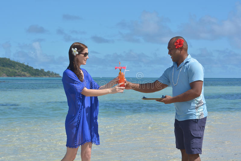 Fijian man serve a tropical cocktail drink to a tourist woman in royalty free stock images