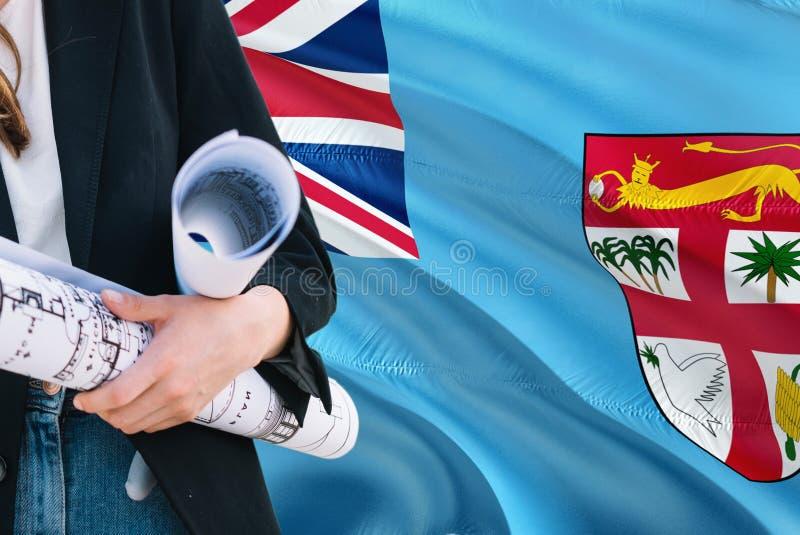Fijian ritning för arkitektkvinnainnehav mot Fiji vinkande flaggabakgrund Konstruktions- och arkitekturbegrepp royaltyfri fotografi