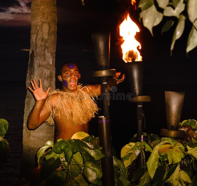 Fijian warrior lighting tiki torch at sunset stock photos