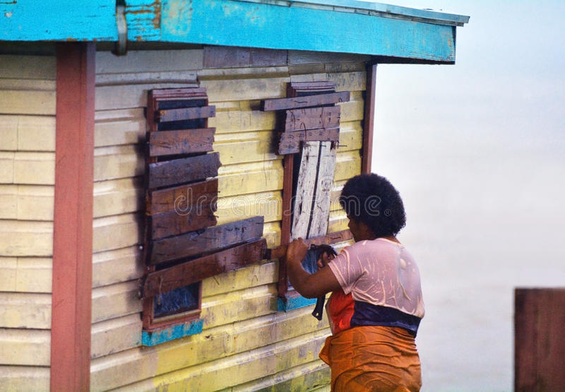 Fijian woman boarding up her house during a Tropical Cyclone. FIJI - DEC 17 2016:Fijian woman boarding up her house during a Tropical Cyclone. On Feb 2016 Severe royalty free stock image