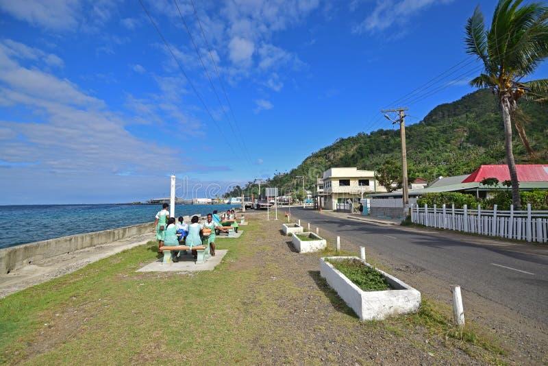 Fijianstudenten, die heraus an der allgemeinen Tabelle und an der Bank auf Ufergegend bei Levuka, Ovalau-Insel, Fidschi hängen lizenzfreies stockfoto