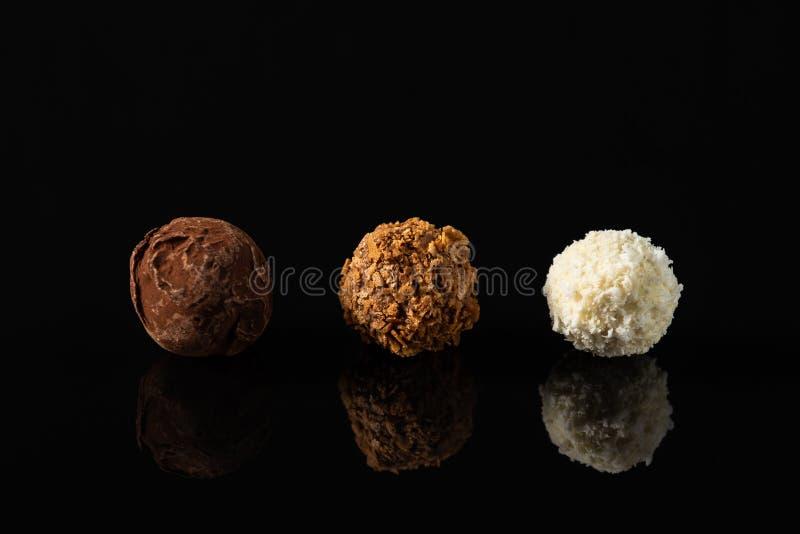 Fijn chocoladesuikergoed op zwarte achtergrond met bezinning Wit, melk en bittere donkere chocolade royalty-vrije stock afbeeldingen