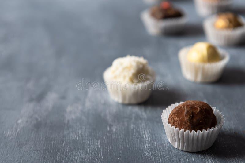 Fijn chocoladesuikergoed, wit, dark en melkchocola op grijze achtergrond De snoepjesachtergrond, zijaanzicht, sluit omhoog, kopie royalty-vrije stock fotografie