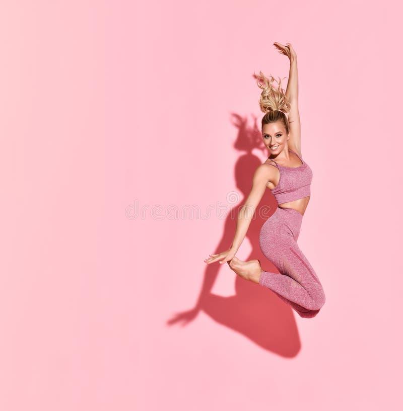 Fijne atletische vrouw die in silhouette springt Foto van een sportieve vrouw in een roze, fashioneerbaar sportvloed op een roze stock afbeelding