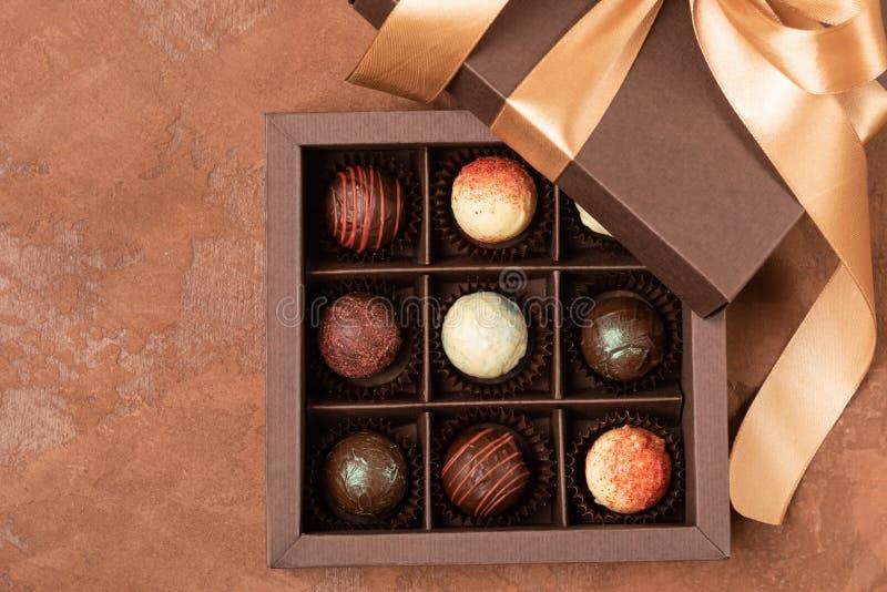 Fijne chocolade in ambachtdoos met satijnlint op een donkere achtergrond Vlakke lay-out Feestelijk concept De ruimte van het exem stock fotografie