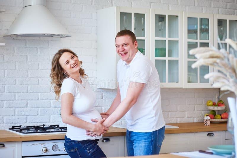 Fijne familie met zwangere vrouwen die in de scandinavische keuken zitten en plezier hebben stock afbeelding