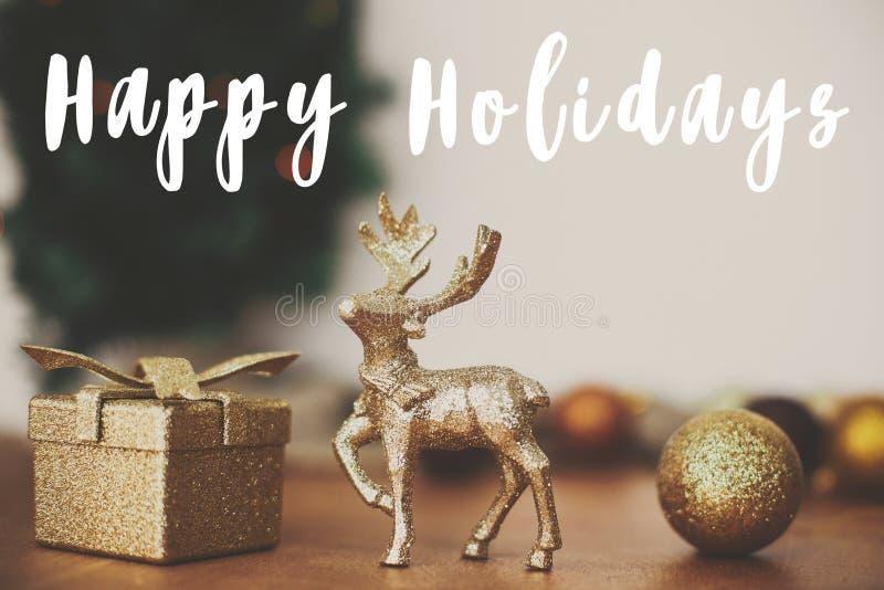 Fijne feestdagen tekenteken op gouden rendieren, cadeaudoosje en glitter bauble toys on background of kersttree with light on royalty-vrije stock foto