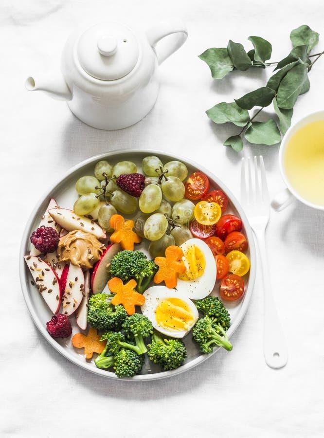 Fijne gezonde vrouwen, ontbijt voor kinderen, snack - groenten, fruit, bessen, gekookt ei en groene thee op een licht stock afbeelding