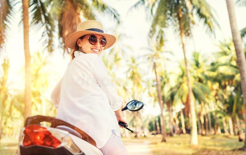 Fijne glimlachende vrouw in riethoed en zonnebril op motorfiets onder de palmbomen Onvermoeibare warme landen vakantietijd royalty-vrije stock foto's