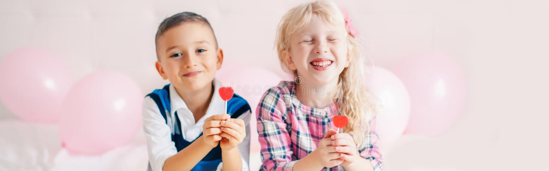 Fijne Kaukasische grappige kinderen die een rode lolly van hun hartafbeelding eten Beste vrienden voor altijd Valentine Day-liefd stock foto's