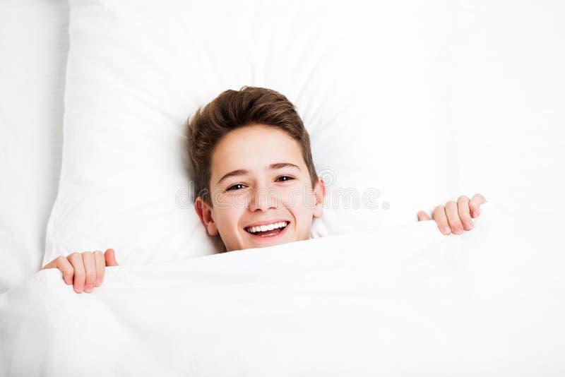 Fijne knappe en lachende kindjongen die bed ligt en rust stock afbeeldingen
