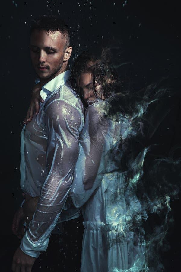Fijne kunstbeeldspraak Onduidelijk beeldportret van romantisch paar in wit overhemd en kleding die zich onder regen bevinden royalty-vrije stock afbeelding