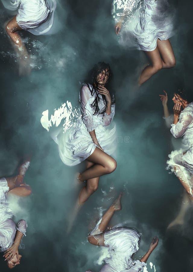 Fijne kunstbeeldspraak Selendermeisje in witte kleding onderwater royalty-vrije stock fotografie