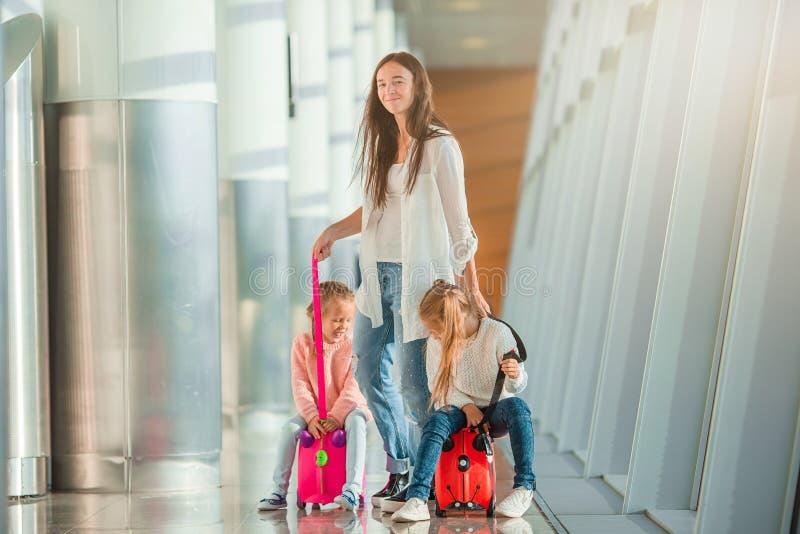 Fijne moeder en kleine meisjes met instapkaart op vliegveld royalty-vrije stock afbeeldingen