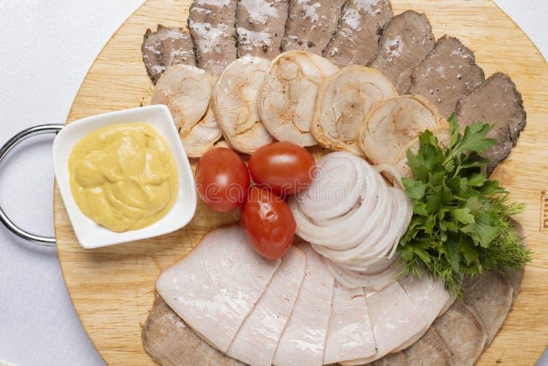 Fijne vleeswaren met peterselie, kaassaus en kersentomaten met uiringen stock foto