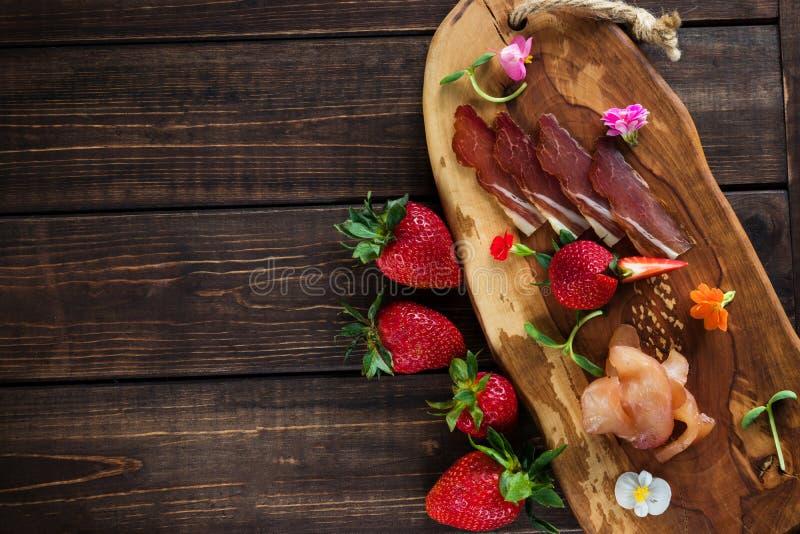 Fijne vleeswaren op een duidelijke achtergrond, een houten raad, aardbeien en micro- greens vrije plaats voor tekst stock afbeelding