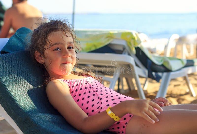Fijne Vrij kleine meid die aan de kust van de zee zit en glimlacht op de zomerzonsondergang stock afbeeldingen