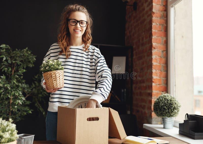 Fijne vrouw nieuwkomer die kartonnen doos uitpakt aan tafel op de nieuwe werkplek in de wc stock afbeelding