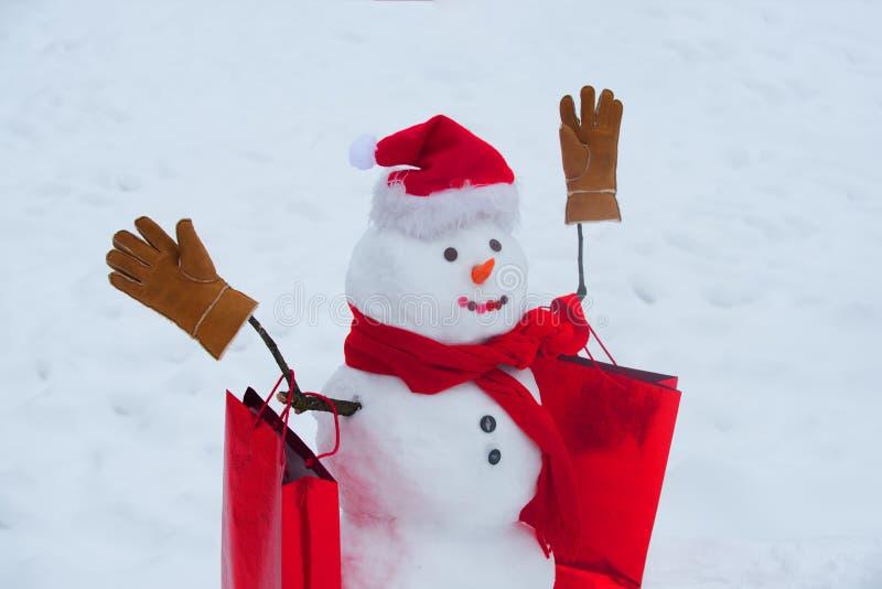 Fijne wintertijd Leveringsgeschenken en cadeauemoties Grappig snowman met een wortel in plaats van een neus en in een warm brei royalty-vrije stock afbeeldingen