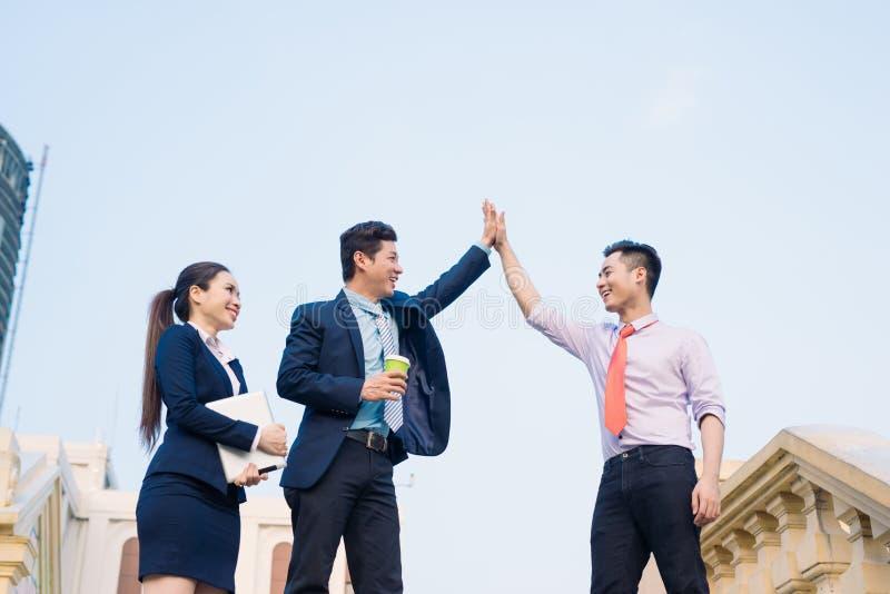Fijne zakenlieden en zakenvrouw vieren succes in de verwezenlijking van de projecttaak stock afbeeldingen