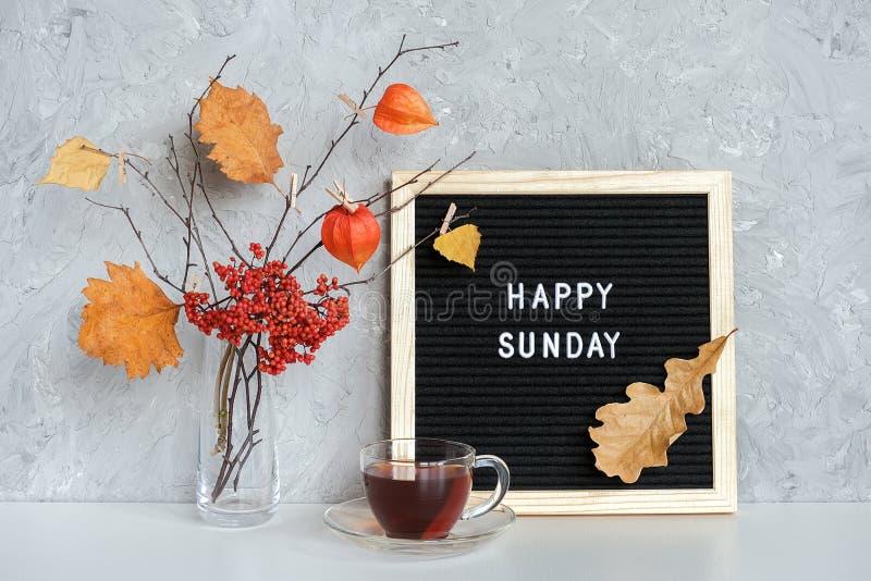 Fijne Zondag tekst op zwarte brievenbus en boeket van takken met gele bladeren op clothespins in vaas en kopje thee op tafel stock foto