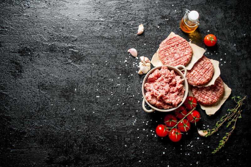 Fijngehakte rundvleeshamburger met tomaten, olie en knoflook royalty-vrije stock afbeeldingen