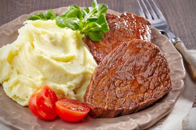 Fijngestampt aardappels en rundvleeslapje vlees stock foto's