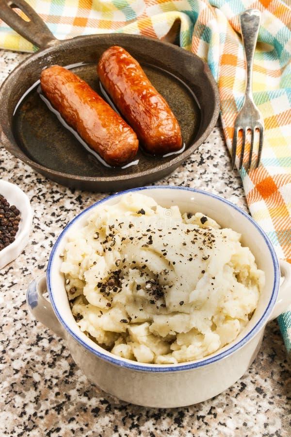 Fijngestampte aardappel met verpletterde zwarte peperbollen en Ierse worsten royalty-vrije stock afbeelding